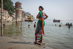 May 18, 2019 - Varanasi, India - On 17 May 2019, an Indian woman in a colorful dress looks over the Ganges River as people bathe themselves in its water, which is considered to be holy under the Hindu religion. Photo taken in the city of Varanasi, India. (Credit Image: © Diego Cupolo/NurPhoto via ZUMA Press)