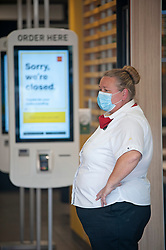 ©Licensed to London News Pictures 13/05/2020<br /> Welling, UK. A member of staff wearing a mask. Welling McDonalds in South East London has queues of food delivery drivers outside waiting. Some McDonalds restaurants in the UK have opened today from 11am for McDelivery service only after being closed for weeks due to the Coronavirus lockdown. Photo credit: Grant Falvey/LNP