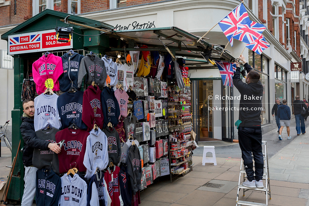 Stallholders set up their outdoors tourist trinkets displays on Oxford Street in the West End, on 5th June 2019, in London, England.