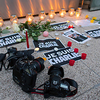 Photojournalists' cameras lay on the ground among flowers and candles placed in support of the Charlie Hebdo satirical weekly in front of the French Institute in Budapest, Hungary on January 08, 2015. ATTILA VOLGYI