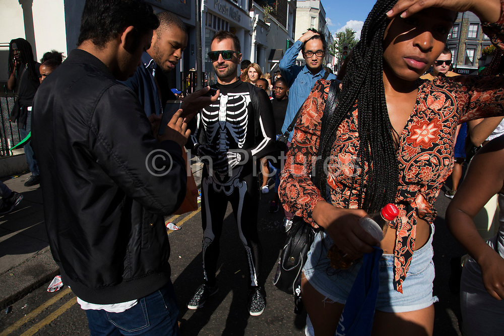 Evening light on Westbourne Park Road on Monday 28th August 2016 at the 50th Notting Hill Carnival in West London. A celebration of West Indian / Caribbean culture and Europes largest street party, festival and parade. Revellers come in their hundreds of thousands to have fun, dance, drink and let go in the brilliant atmosphere. It is led by members of the West Indian / Caribbean community, particularly the Trinidadian and Tobagonian British population, many of whom have lived in the area since the 1950s. The carnival has attracted up to 2 million people in the past and centres around a parade of floats, dancers and sound systems.