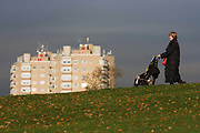 A middle-aged lady pushes a child through an urban park that has a high-rise tower block of flats as a backdrop. Seen from Brockwell Park, Herne Hill, South London, the woman may be the infant's grandmother (granny) and possibly helping the child's mother during an afternoon walk among autumn leaves that lie across the grass. There is a downhill slope and the lady holds on to the buggy in case it rolls down the hill. The flats behind are lit in winter sunshine, warm air rising from an outlet, with only the upper floors visible to outdoor pedestrians. Brockwell Park is a 50.8 hectare (125.53 acres) park located between Brixton, Herne Hill and Tulse Hill. Brockwell Hall house and its grounds were acquired by the London County Council (LCC) in March 1891 and opened to the public the following summer.