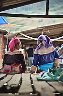 Hmong women wearing traditional clothes chat while sitting on a wooden stand in a small village market in Lao Cao Province, Bac Ha District, Northern Vietnam, Southeast Asia