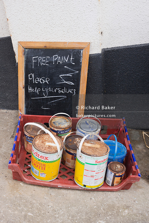 A community spirited sign urges villagers to help themselves to rusted paint pots in the north Devon village of Mortehoe.