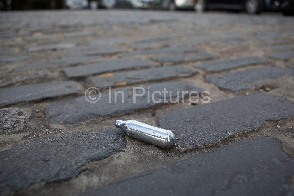 """Small empty cannister of laughing gas lying on the street. Nitrous oxide, commonly known as laughing gas, nitrous, nitro, or NOS is now a very common 'legal high' used by young people. Nitrous oxide can cause analgesia, depersonalisation, derealisation, dizziness, euphoria, and some sound distortion. Inhalation of nitrous oxide for recreational use, with the purpose of causing euphoria and/or slight hallucinations, began as a phenomenon for the British upper class in 1799, known as """"laughing gas parties""""."""