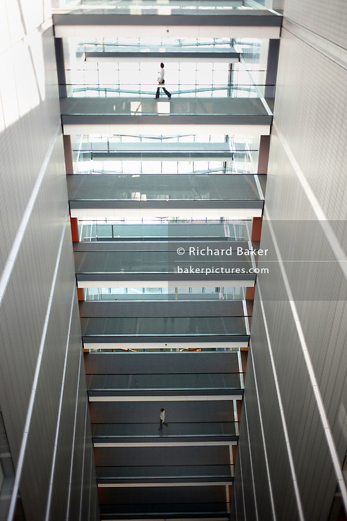 Separated by four floors, two employees of the auditing company Ernst & Young, make their way along walkways in the main atrium of E & Y's European headquarter offices at More London, London England. Striding confidently between offices, the two people are unaware of each other's presence but make their way from right to left of this tall, upright scene of modernity. The senior person on top may have an advantage from better opportunities, the low-ranking worker below may be needing to rise up the ranks. Morning sunlight floods through the green tinted glass that overlooks Tower Bridge on the River Thames. The term atrium comes from Latin: a large and light central hall or reception of a house where guests were greeted. The depth and height of all levels from near the top to almost the bottom give a sense of vertigo, a dizzying perspective. .