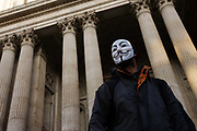 An anti-capitalist activist wears an Anonymous mask below the pillars and columns of the Sir Christopher Wren-designed St Paul's Cathedral on the 11th day of the Occupy London protest camp in its churchyard, London 26/11/11. Forced to close for the first time since the 2nd world war, due to health and safety concerns, preventing services City lawyers are using medieval pedestrian bylaws to gain a court injunction to evict the activists who set up tents and shelters.