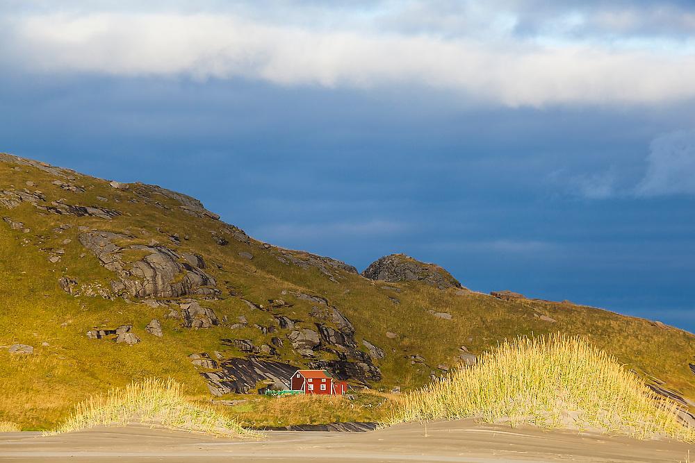 A lone cabin framed by small sand dunes on Bunes Beach, Moskenesoya, Lofoten Islands, Norway.