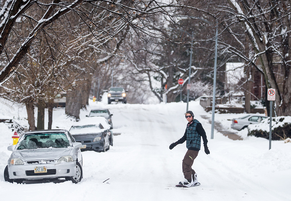 Cody Oltrogge snowboards down Cass Street while taking a break from shoveling in Midtown on Tuesday, Feb. 2, 2016, in Omaha.