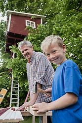Grandfather grandson working together tree-house