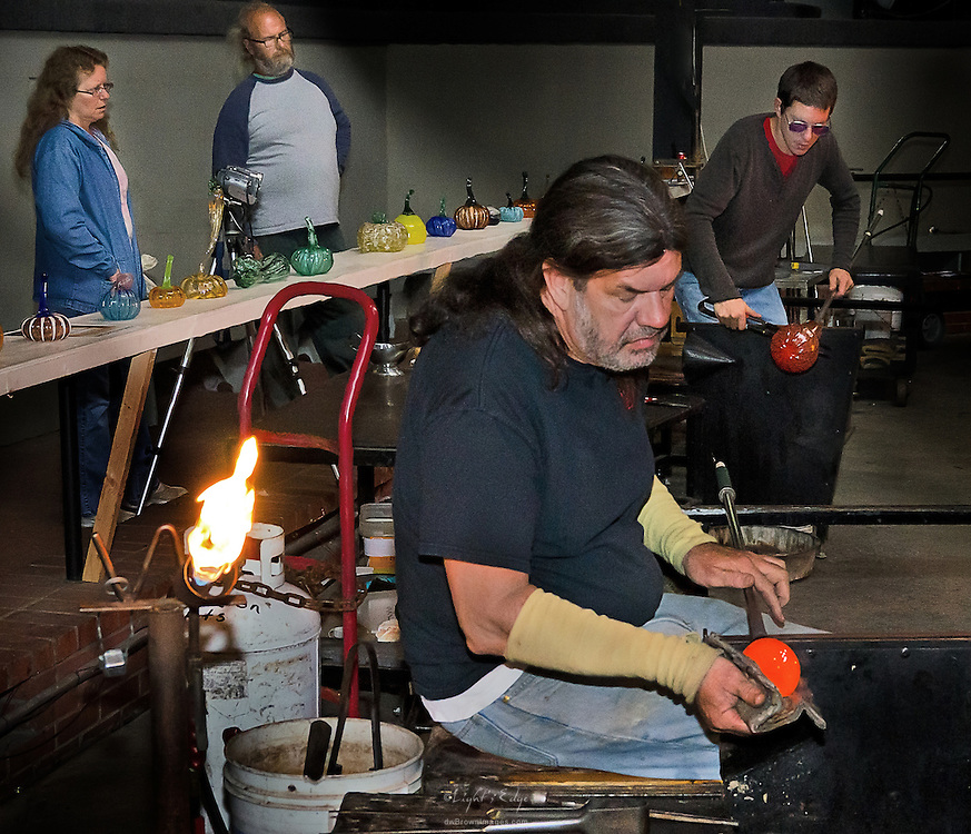 Two artisans work on glass pieces while a couple of visitors observe their craftmanship.