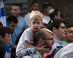 "© Licensed to London News Pictures . 05/06/2016 . Jerusalem , Israel . A youngster wearing a home-made "" Jerusalem "" hat . Thousands of Jews process through the Old City's Muslim district , on the way to the Western Wall , separated from residents of the Old City's Muslim district by Israeli soldiers . Israeli Jews celebrate Jerusalem Day . Photo credit : Joel Goodman/LNP"