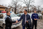 Roma activist Marius Tudor shaking hands with a local police officer in front of the town hall in Filipestii de Targ to which Marginenii de Jos belongs.