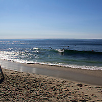 USA, California, San Diego. WindanSea Beach with skimboarder watching surfers.