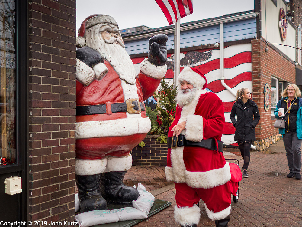 """30 NOVEMBER 2019 - WEST DES MOINES, IOWA: SANTA CLAUS walks past a Santa statue and American flag mural on 5th Street, the main business street in West Des Moines, Saturday. He was handing out gifts to children on Small Business Saturday. """"Small Business Saturday"""" was first observed in the United States on November 27, 2010, as a counterpart to Black Friday and Cyber Monday, which are generally considered events at malls, """"big box"""" stores and e-commerce retailers. Small Business Saturday encourages holiday shoppers to patronize brick and mortar businesses that are small and local. Small Business Saturday is a registered trademark of American Express.     PHOTO BY JACK KURTZ"""