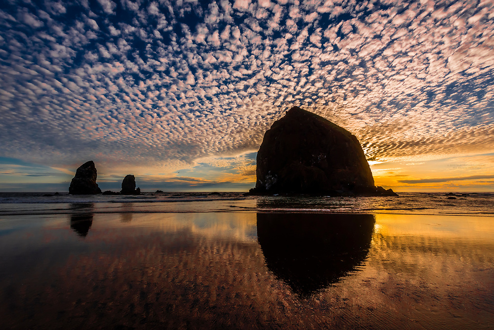 Haystack Rock (with The Needles on left) at sunset, Cannon Beach, Oregon USA.