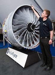 © London News Pictures. 09/07/2012. Farnborough, UK. Rolls Royce Manufacturing Engineering graduate trainee Dusty Orton attaching a piece to a giant Rolls Royce engine made 152,000 pieces of Lego on day one of the Farnborough International Airshow, in Farnborough, Hampshire, UK on July 9, 2012. FIA is a seven-day international trade fair for the aerospace industry which is held every two years at Farnborough Airport . Photo credit: Ben Cawthra/LNP.