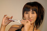 An exhibition promotion girl demonstrates a mobile phone that can be played as a flute. The camera senses movement which it turns into musical notes.
