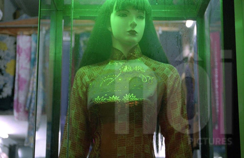 Through a window display, a mannequin wearing traditional ao dai is lit with a green light Hanoi, Vietnam, Asia