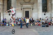 A street performer is helped onto a unicycle by members of the audience in from of St Paul's Church (commonly known as the Actors' Church) Covent Garden Market, London, UK