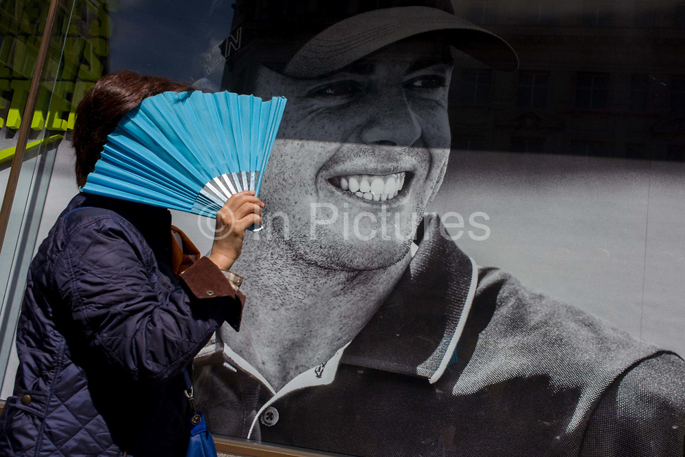 Woman with fan shielding her face from sunchine passes a Nike retail poster of Northern Irish golfer Rory McIlroy, in central London. The scene has a theme of smiles and smiling faces with the teeth of the British golfing hero, sponsored by the Nike brand.