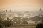 Sunrise looking out over the temples of Bagan. It is an ancient city in central Myanmar (formerly Burma), southwest of Mandalay. Standing on the eastern banks of the Ayeyarwady River, it's known for the Bagan Archaeological Area, where more than 2,000 Buddhist monuments tower over green plains.