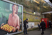 A rail passenger momentarily holds a sandwich in his mouth beneath an advertising billboard for home baked spicy wraps, on the platform at Denmark Hill rail station, on 14th February 2020, in London, England. Denmark Hill station is a small south rail hub with routes on the south London Overground loop and lines between London Victoria and Kent.