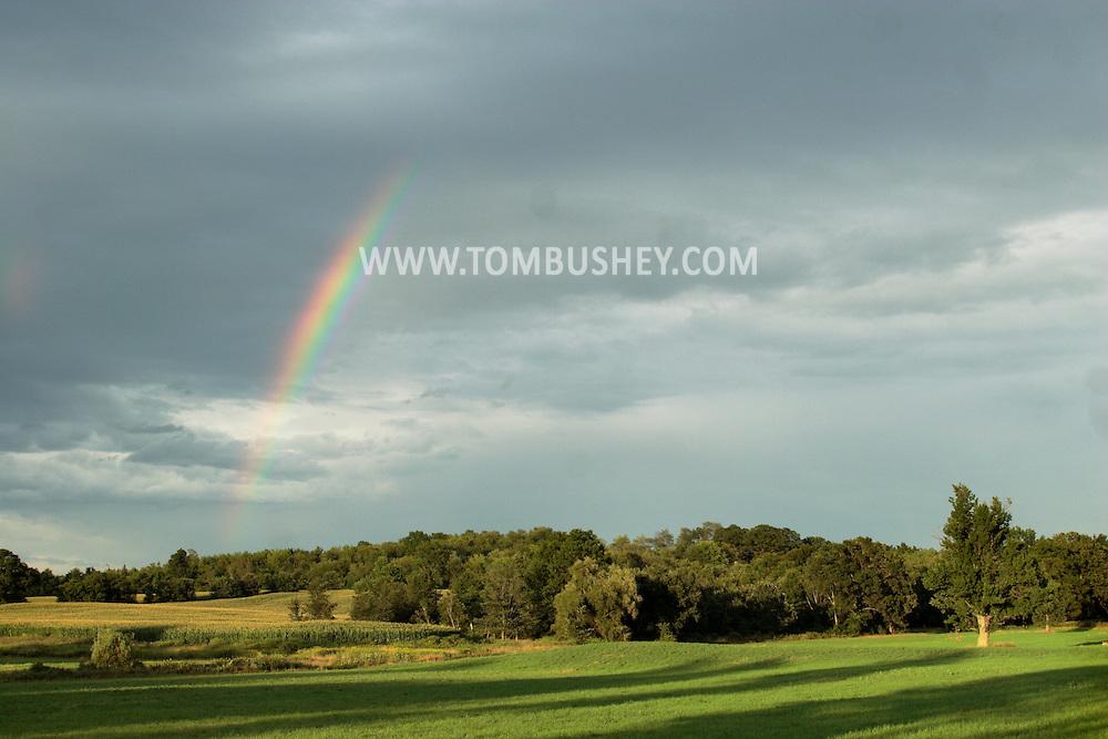 Montgomery, NY - A rainbow arcs across the sky behind farm fields on Aug. 2, 2008.