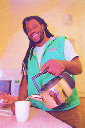 Resident living in 'moveon' flat of homeless hostel making cup of tea in kitchen,