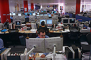 "An analyst for the Enron Corporation, the American energy company based in Houston, Texas, stares transfixed into two computer monitors in the London office at Grosvenor Place, opposite the Queen's official residence, Buckingham Palace. Two Cross of St George flags perch to the tops of the screens. Informal dress was practised in this Enron company building before its eventual bankruptcy in late 2001, Enron employed around 21,000 people  and was one of the world's leading electricity, natural gas, pulp and paper, and communications companies, with claimed revenues of $111 billion in 2000. Fortune named Enron ""America's Most Innovative Company"" but has since become a popular symbol of willful corporate fraud and corruption."