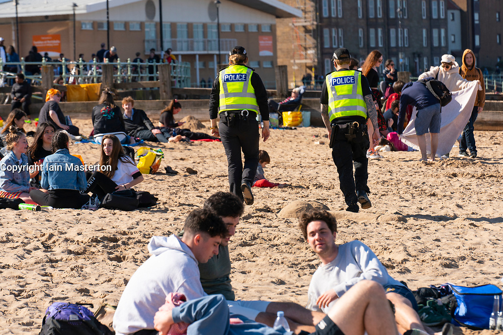 Portobello, Scotland, UK. 3 April 2021. Easter weekend crowds descend on Portobello beach and promenade to make the most of newly relaxed  Covid-19 lockdown travel restrictions and warm sunshine with uninterrupted blue skies. Pic; Low key police foot patrol along the beach but nobody was spoken to by the police officers. Iain Masterton/Alamy Live News