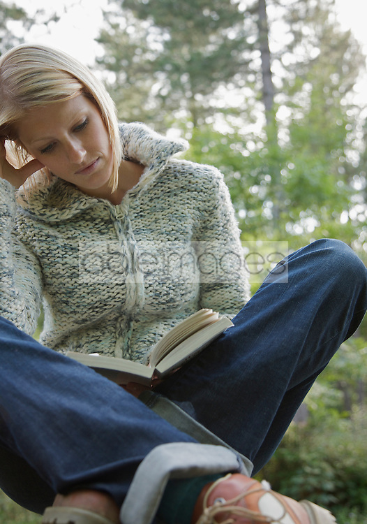 Young woman sitting cross legged in a forest reading a book