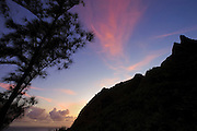 A colorful autumn sunrise colors the sky above Maunapuluo, a mountain on the north side of the Hawaiian island of Kauai on the Na Pali Coast.