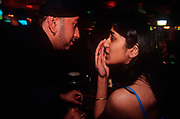 Two 1990s British Asians talk discreetly at a club in West London, on 16th August 1998, innLondon, England.