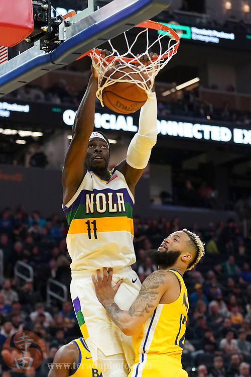 February 23, 2020; San Francisco, California, USA; New Orleans Pelicans guard Jrue Holiday (11) dunks the basketball against Golden State Warriors guard Ky Bowman (12) during the fourth quarter at Chase Center.