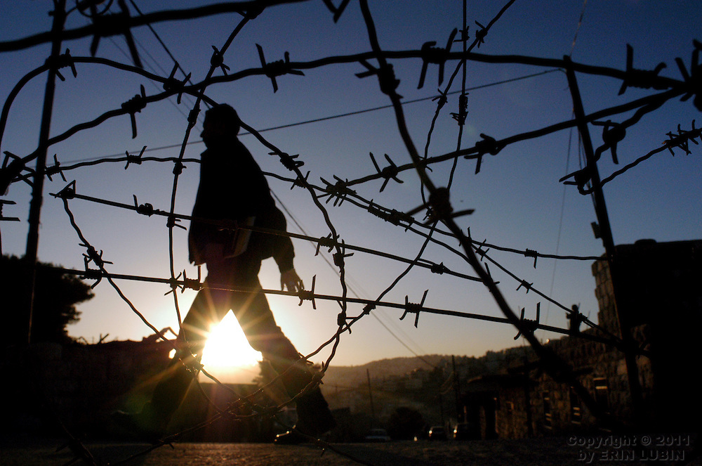 A man walks past a bundle of barbed wire laying on the street in Abu Dis, a Palestinian town outside of East Jerusalem on November 15, 2003...Photo by Erin Lubin
