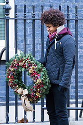 London, December 01 2017. Workers install the Christmas tree outside the door of 10 Downing Street, official residence of the British Prime Minister. The tree comes from the winner of the British Christmas Tree Growers' Association' annual competition for the honour of having a grower's tree at the prestigious address. PICTURED: Blue Peter's Radzi Chinyanganya holds the wreath for the door. © Paul Davey