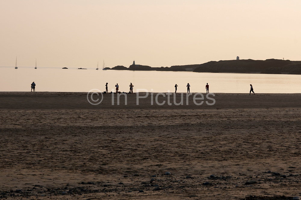 People playing games at sunset on Newborough Beach on 17th September 2020 in Newborough, Anglesey, Wales, United Kingdom. Known in Welsh as Llanddwyn Beach, it is a Blue Flag Beach backed by Newborough National Nature Reserve and forest on the south-western tip of Anglesey.
