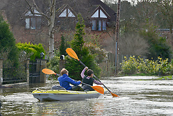 © Licensed to London News Pictures. 09/02/2014. Wraysbury, UK. Young boys play on a flooded road in a canoe. Flooding in Wraysbury in Berkshire today 9th February 2014 after the River Thames burst its banks. Photo credit : Stephen Simpson/LNP