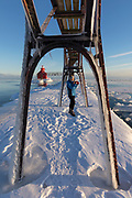 A teenage girl takes pictures at a lighthouse on Lake Michigan in Sturgeon Bay, Wisconsin on a cold winter day.
