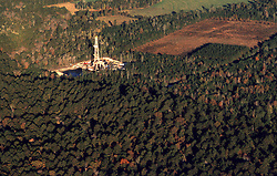 Stock photo of the aerial view of an on-shore rig site in the middle of a forested area