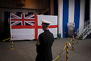 A Chief Petty Officer near the Navy's Ensign flag on the hangar deck during a tour by the general public on-board the Royal Navy's aircraft carrier HMS Illustrious during a public open-day in Greenwich. Illustrious docked on the river Thames, allowing the tax-paying public to tour its decks before its forthcoming decommisioning. Navy personnel helped with the PR event over the May weekend, historically the home of Britain's naval fleet.