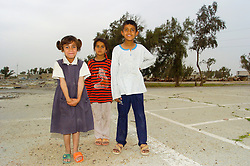 Iraqi Children pose for their picture taking on an old car park near the Iraq, Kuwait border after approaching a British military Patrol. The girl on the far left is dressed in odd sandals, the image was shot in March 2005 during Op Telic V