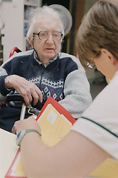 Female occupational therapist talking to elderly man in a wheelchair; making an assessment on progress,