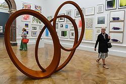 "© Licensed to London News Pictures. 08/06/2017. London, UK. A visitor passes by a scuplture called ""Natural Pearl"" by Nigel Hall RA (GBP189,600).  Preview of the Summer Exhibition 2017 at the Royal Academy of Arts in Piccadilly.  Co-ordinated by Royal Academician Eileen Cooper, the 249th Summer Exhibition is the world's largest open submission exhibition with around 1,100 works on display by high profile and up and coming artists.<br />  Photo credit : Stephen Chung/LNP"