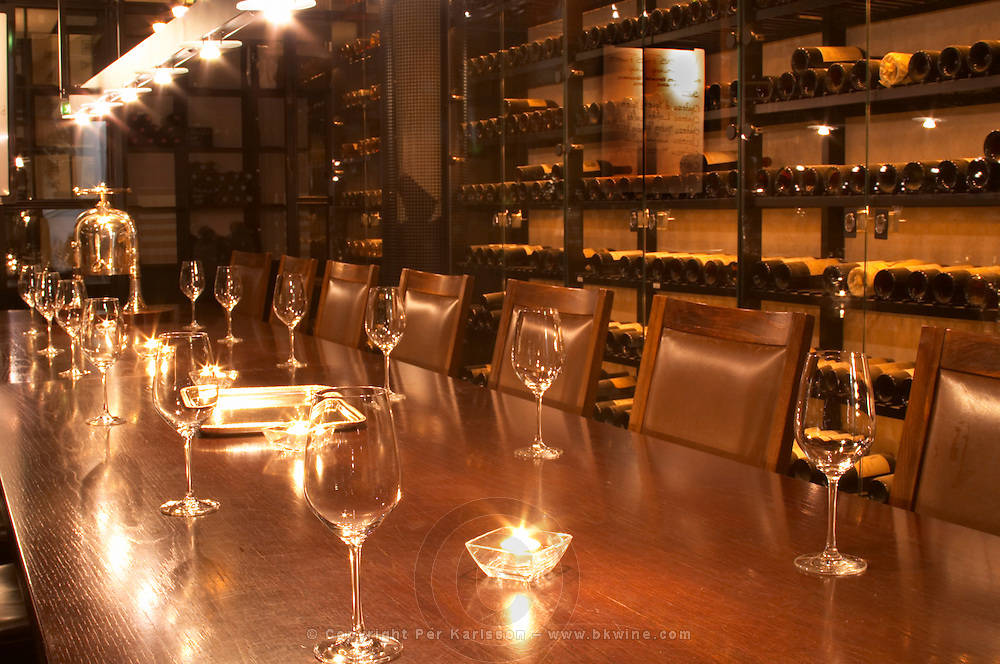 A wine tasting room with glasses on the table and lit candles. Wine racks with old wine bottles in the background. Ulriksdal Ulriksdals Wärdshus Värdshus Wardshus Vardshus Restaurant, Stockholm, Sweden, Sverige, Europe