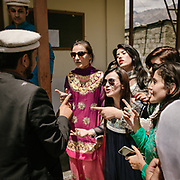 Traditional game while coming out of the Jama Khana: girlfriend and relative of the bride arguing the price of the groom's shoes with a man from the groom's family.