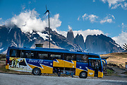 A bus awaits passengers. The namesake towers of Torres del Paine National Park can be seen from Laguna Amarga Entrance and Range Station. Ultima Esperanza Province, Chile, Patagonia, South America. The Park is listed as a World Biosphere Reserve by UNESCO.