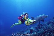 JoJo, a wild sociable bottlenose dolphin, Tursiops truncatus, follows a scuba diver with an underwater scooter, Turks and Caicos ( Western Atlantic Ocean ) MR 147
