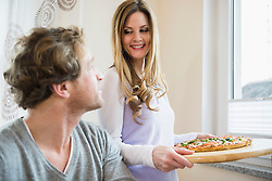 Woman serving pizza watched by man
